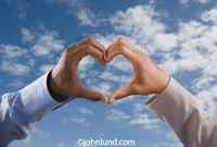 Multi-ethnic hands making heart-shape formation. Slightly cloudy sky. Male hands.